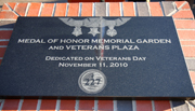 A new black granite marker is inscribed with an image of the medals and the plaza's name.